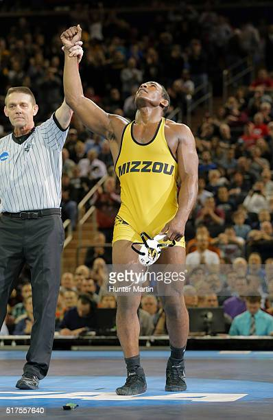 Den Cox of the Missouri Tigers gets his hand raised after defeating Morgan McIntosh of the Penn State Nittany Lions during the finals of the NCAA...