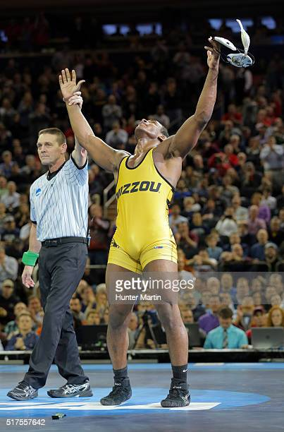 Den Cox of the Missouri Tigers raises his hands after defeating Morgan McIntosh of the Penn State Nittany Lions during the finals of the NCAA...
