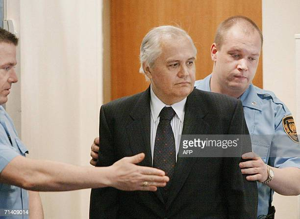 Former Serbian president Milan Milutinovic is escorted by two guards into the courtroom of the UN warcrimes tribunal in the Hague 27 January 2003 The...