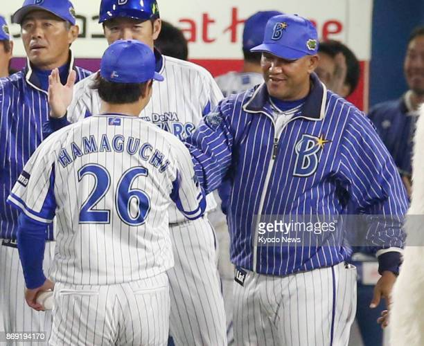 DeNA BayStars manager Alex Ramirez congratulates rookie pitcher Haruhiro Hamaguchi on his first win of the Japan Series after the BayStars' 60...