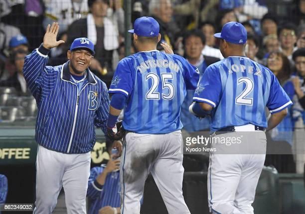 DeNA BayStars manager Alex Remirez highfives with left fielder Yoshitomo Tsutsugo and first baseman Jose Lopez after a 61 win over the Hanshin Tigers...
