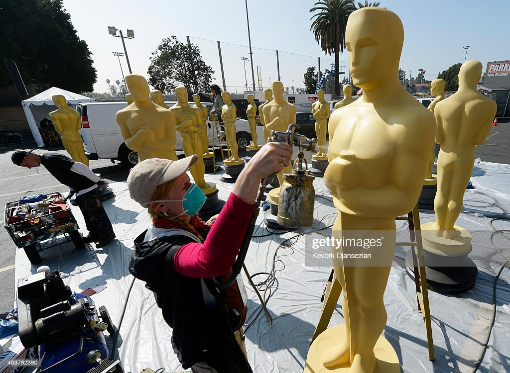 Dena D'Angelo spray paints an Oscar statue with gold paint during preparation of 87th Annual Academy Awards at Dolby Theater February 18 2015 in...