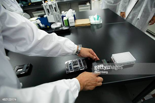 DeNA Life Science Inc employee Hiroki Furuhashi displays microarray chips used for genetic analysis for the company's directtoconsumer genetic...