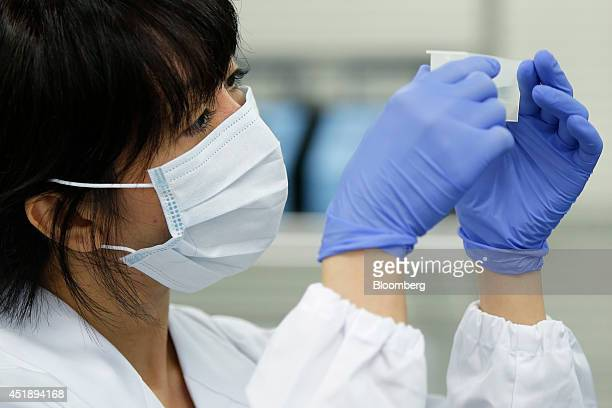 A DeNA Life Science Inc laboratory technician checks a reagent to be added to plates containing genes extracted from a customer's saliva in...