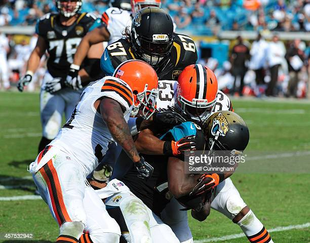 Denard Robinson of the Jacksonville Jaguars is tackled by Craig Robertson and Donte Whitner of the Cleveland Browns at EverBank Field on October 19...