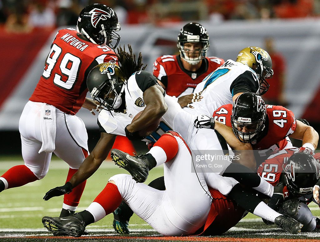 <a gi-track='captionPersonalityLinkClicked' href=/galleries/search?phrase=Denard+Robinson&family=editorial&specificpeople=6234939 ng-click='$event.stopPropagation()'>Denard Robinson</a> #16 of the Jacksonville Jaguars tackles by Stansly Maponga #99, Adam Replogle #67, Joplo Bartu #59, and Paul Worrilow #49 of the Atlanta Falcons at Georgia Dome on August 29, 2013 in Atlanta, Georgia.