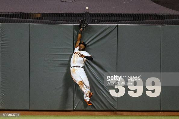Denard Span of the San Francisco Giants leaps for but is unable to catch a fly ball hit for a home run by Welington Castillo of the Arizona...