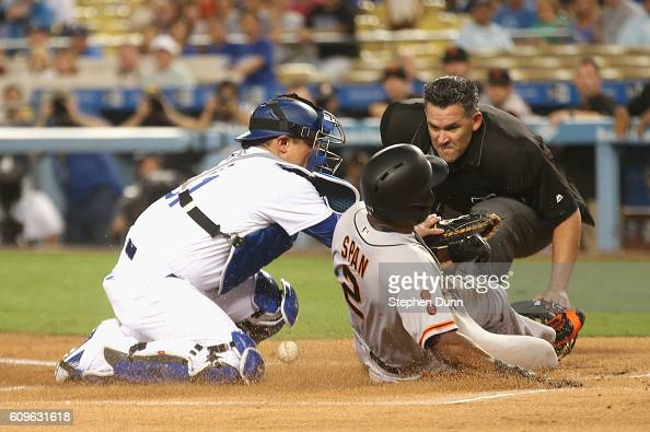 Denard Span of the San Francisco Giants slides home safely to score a run in the first inning as catcher Carlos Ruiz of the Los Angeles Dodgers can't...