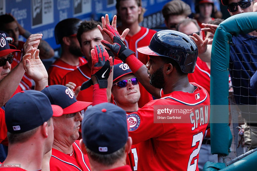 <a gi-track='captionPersonalityLinkClicked' href=/galleries/search?phrase=Denard+Span&family=editorial&specificpeople=835844 ng-click='$event.stopPropagation()'>Denard Span</a> #2 of the Washington Nationals is congratulated by teammates in the dugout after scoring in the ninth inning of the game against the Philadelphia Phillies at Citizens Bank Park on July 13, 2014 in Philadelphia, Pennsylvania. The Nationals won 10-3.