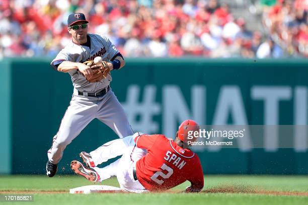 Denard Span of the Washington Nationals is out at second base as Brian Dozier of the Minnesota Twins makes a throw to first base to turn a double...