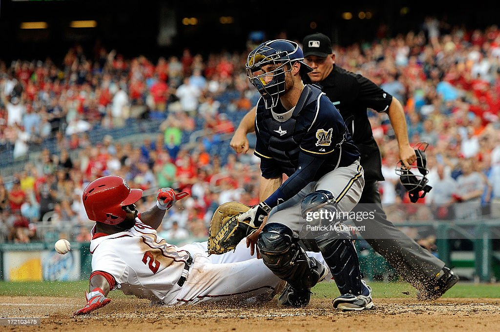 <a gi-track='captionPersonalityLinkClicked' href=/galleries/search?phrase=Denard+Span&family=editorial&specificpeople=835844 ng-click='$event.stopPropagation()'>Denard Span</a> #2 of the Washington Nationals slides safely into home plate past <a gi-track='captionPersonalityLinkClicked' href=/galleries/search?phrase=Jonathan+Lucroy&family=editorial&specificpeople=5732413 ng-click='$event.stopPropagation()'>Jonathan Lucroy</a> #20 of the Milwaukee Brewers on a two run RBI double by Jayson Werth #28 in the third inning during a game at Nationals Park on July 1, 2013 in Washington, DC.