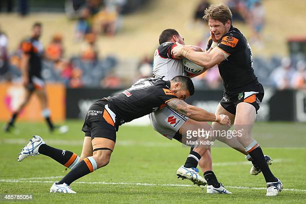 Dene Halatau and Chris Lawrence of the Wests Tigers tackle Bodene Thompson of the Warriors during the round 25 NRL match between the Wests Tigers and...