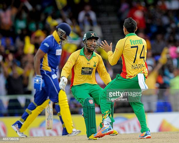 Denesh Ramdin and Sunil Narine of Guyana Amazon Warriors celebrate Kieron Pollard of Barbados Tridents dismissal during the Limacol Caribbean Premier...