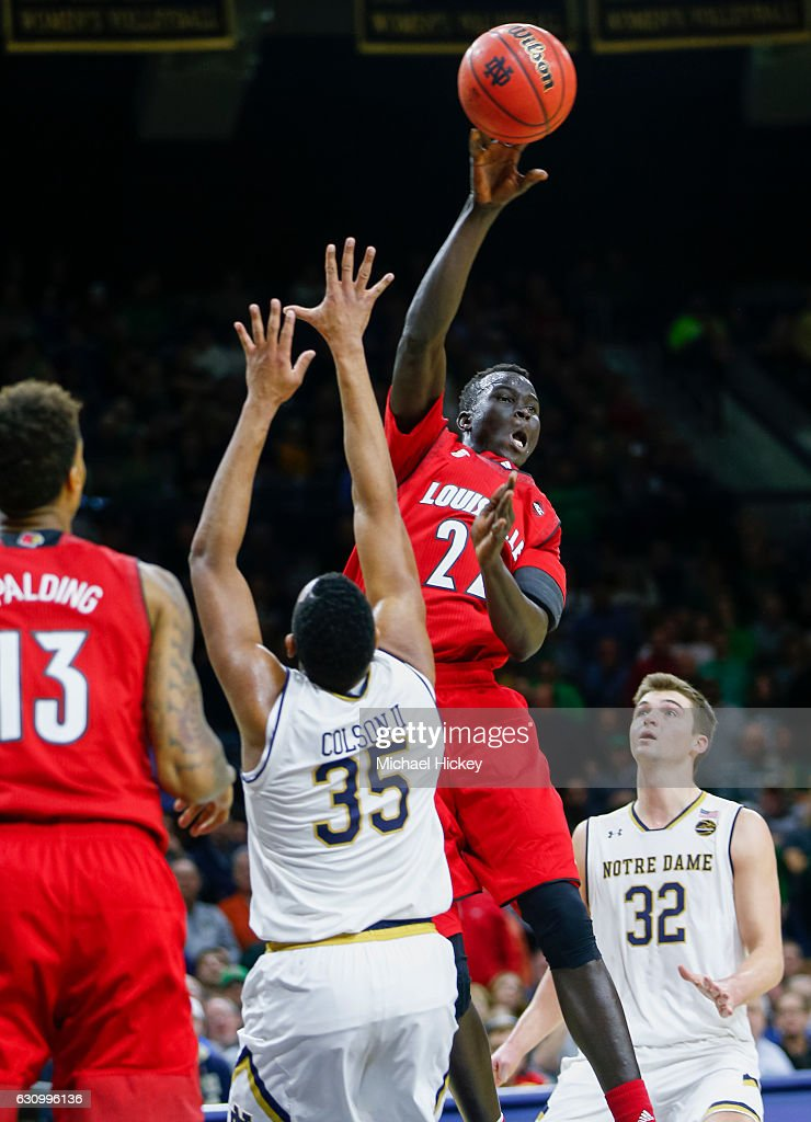 Deng Adel #22 of the Louisville Cardinals passes the ball off as Bonzie Colson #35 of the Notre Dame Fighting Irish defends at Purcell Pavilion on January 4, 2017 in South Bend, Indiana.