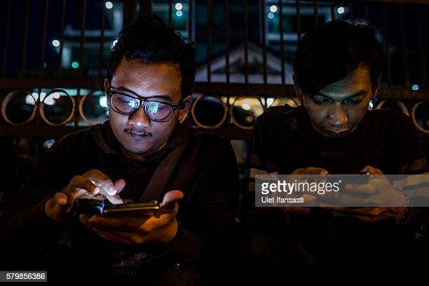 Deni plays Pokemon Go game on his smartphone on July 24 2016 in Yogyakarta Indonesia 'Pokemon Go' which uses Google Maps and a smartphone has been a...