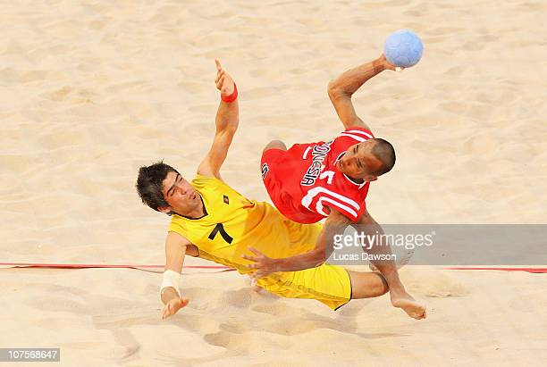 Deni Wahyudin of Indonesia is challenged by Ahmad Azizi of Afghanistan in the Beach Handball match between Indonesia and Afghanistan at AlMusannah...