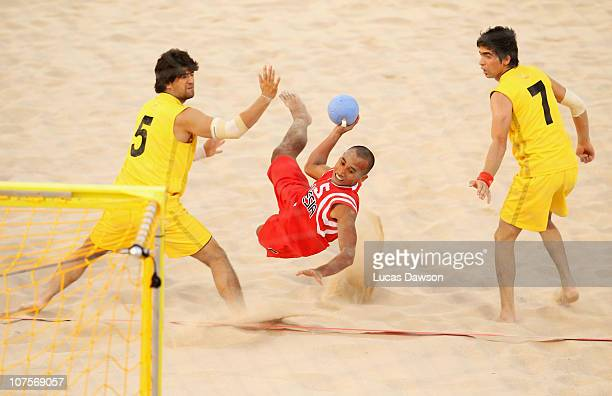 Deni Wahyudin of Indonesia shoots at goal challenged by Shafi Tajzada of Afghanistan in the Beach Handball match between Indonesia and Afghanistan at...