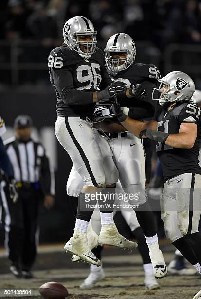 Denico Autry Leon Orr and Ben Heeney of the Oakland Raiders celebrates after Autry sacked Philip Rivers of the San Diego Chargers in the endzone for...