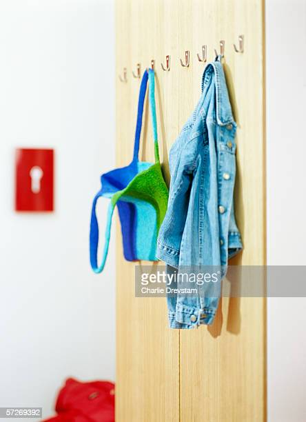 A denim jacket and a bag on clothes hooks in a hall.