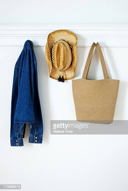 Denim shirt, straw hat and bag hanging on pegs.