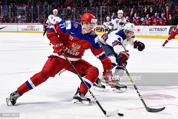 Denis Guryanov of Team Russia skates the puck against Caleb Jones of Team United States during the 2017 IIHF World Junior Championship semifinal game...