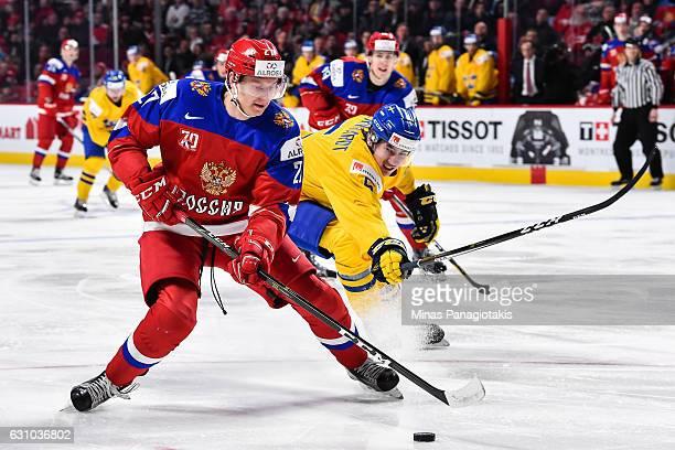 Denis Guryanov of Team Russia skates the puck against David Bernhardt of Team Sweden during the 2017 IIHF World Junior Championship bronze medal game...