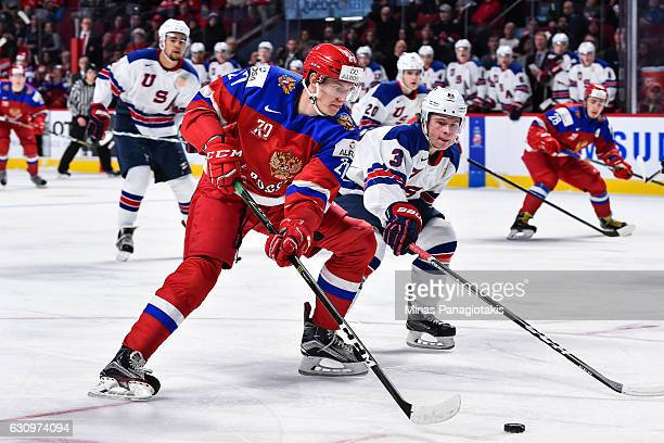 Denis Guryanov of Team Russia skates the puck against Jack Ahcan of Team United States during the 2017 IIHF World Junior Championship semifinal game...