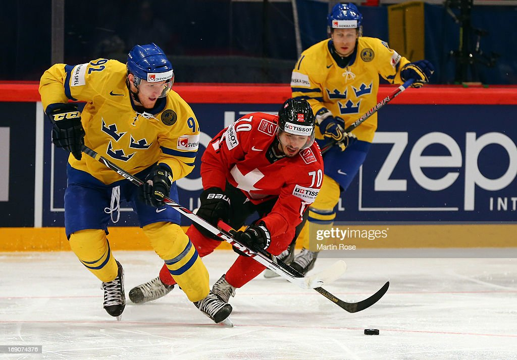 Denis Hollenstein (R) of Swiss and Gabriel Landeskog (L) of Sweden battle for the puck during the IIHF World Championship final match between Swiss and Sweden at Globen Arena on May 19, 2013 in Stockholm, Sweden.
