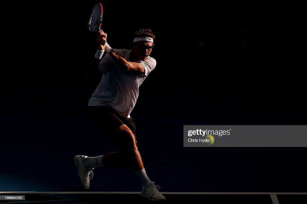 Denis Istomin of Uzbekistan plays a backhand during his match against Lleyton Hewitt of Australia on day five of the Brisbane International at Pat Rafter Arena on January 3, 2013 in Brisbane, Australia.