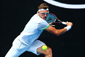 Denis Istomin of Uzbekistan plays a backhand in his first round match against Bernard Tomic of Australia during day two of the 2016 Australian Open...