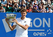 Denis Istomin of Uzbekistan poses with the trophy after victory over Sam Querrey of USA during the mens singles final match on day seven of the Aegon...