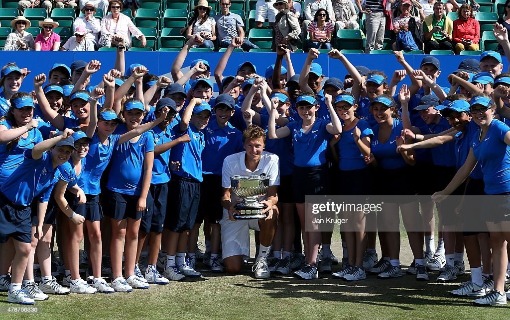 Denis Istomin of Uzbekistan poses with the trophy and ball kids after victory over Sam Querrey of the United States during the mens singles final match on day seven of the Aegon Open Nottingham at Nottingham Tennis Centre on June 27, 2015 in Nottingham, England.