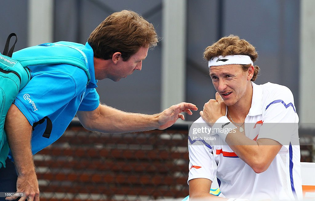 Denis Istomin of Uzbekistan receives attention for a shoulder injury in his quaterfinal match against Kevin Anderson of South Africa during day five of the Sydney International at Sydney Olympic Park Tennis Centre on January 10, 2013 in Sydney, Australia.
