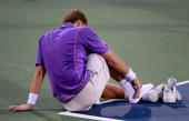 Denis Istomin of Uzebekistan sits down on the court after rolling his right ankle in his match against Roger Federer of Switzerland during Day 3 of...