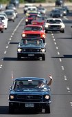 Denis Jones and Vickie Steel both from Takapuna wave from their Ford Mustang as they lead a group of Mustangs on Auckland's Southern Motorway New...