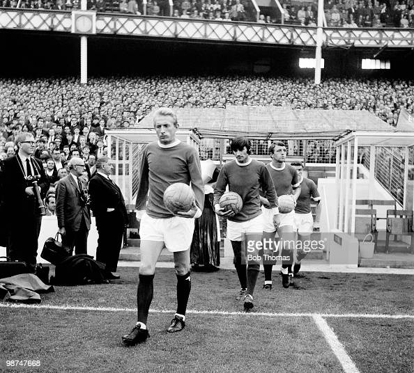 Denis Law is followed by George Best and David Herd as Manchester United enter the field at Goodison Park prior to their match against Everton in...