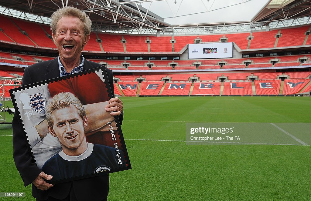 <a gi-track='captionPersonalityLinkClicked' href=/galleries/search?phrase=Denis+Law+-+Soccer+Player&family=editorial&specificpeople=15746096 ng-click='$event.stopPropagation()'>Denis Law</a> jokes around as he poses with his stamp during the Royal Mail Stamp Launch at Wembley Stadium on May 8, 2013 in London, England.