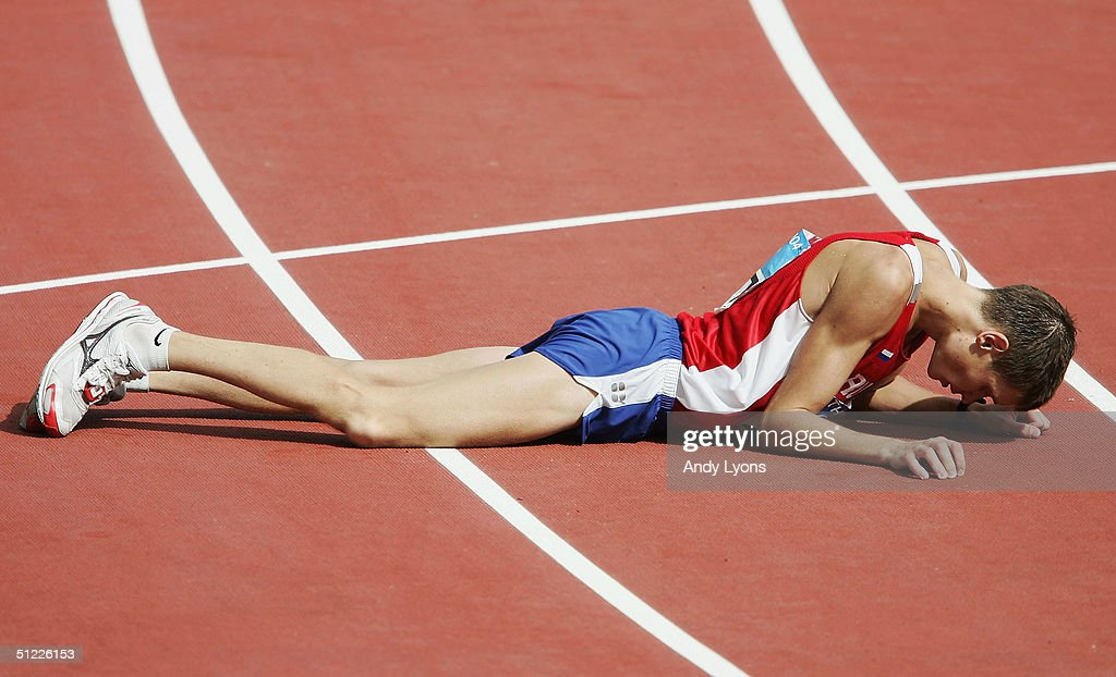 Denis Nizhegorodov of Russia lays down after crossing the finish line to win the silver medal in the men's 50 kilometer race walk after getting red...