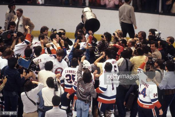 Denis Potvin of the New York Islanders hoists the Stanley Cup after the Islanders defeated the Edmonton Oilers 42 in Game Four of the 1983 Stanley...