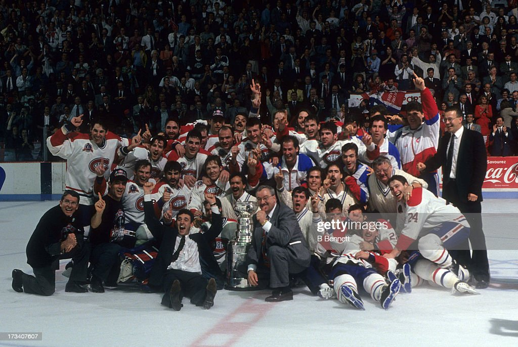 Denis Savard of the Montreal Canadiens celebrates with the Stanley Cup Trophy and his teammates during the team photo after defeating the Los Angeles...