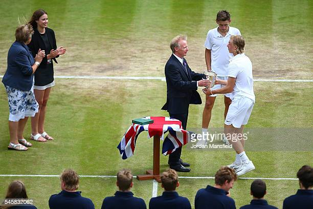Denis Shapovalov of Canada is presented with the trophy following victory during the Boy's Singles Final against Alex De Minaur of Australia on day...