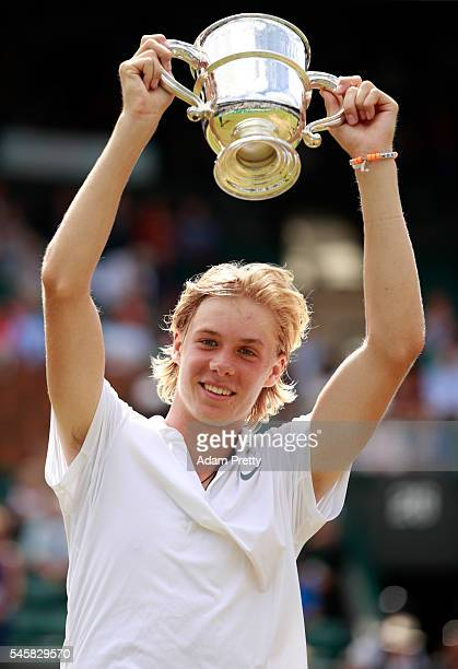 Denis Shapovalov of Canada lifts the trophy as celebrates victory during the Boy's Singles Final against Alex De Minaur of Australia on day thirteen...