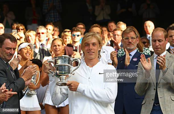 Denis Shapovalov of Canada lifts the trophy following victory during the Boy's Singles Final against Alex De Minaur of Australia on day thirteen of...