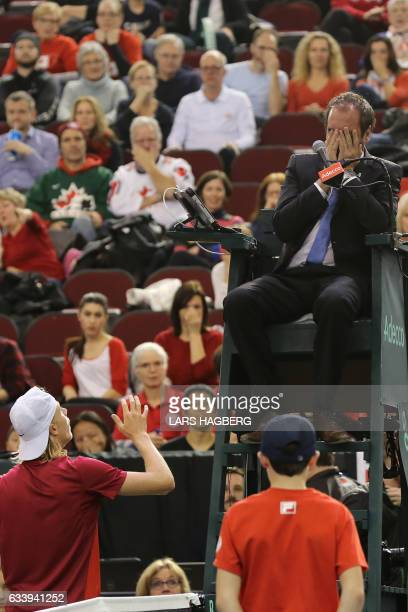 Denis Shapovalov of Canada reacts after accidentaly hitting the head umpire Arnaud Gabas from France during third set action against Kyle Edmund of...