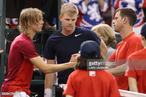 Denis Shapovalov of Canada shake hands with Great Britain coach Leon Smith and Kyle Edmund of Great Britain on the third day of Davis Cup first round...