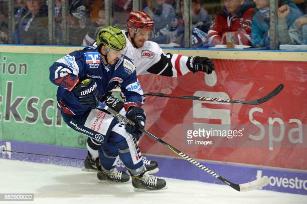 Denis Shevyrin of Iserlohn Roosters and Moritz Mueller of Koeln battle for the ball during the DEL match between Iserlohn Roosters and Kölner Haie on...