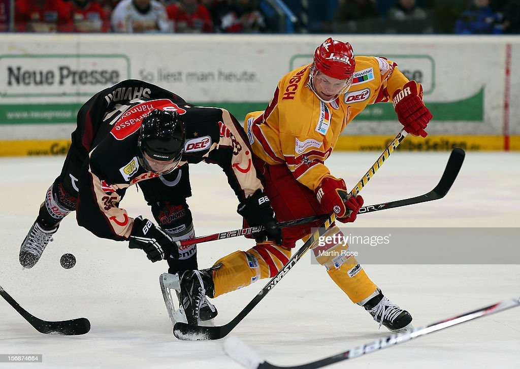 Denis Shvidki (L) of Hannover and Alexander Preibisch (R) of Duesseldorf battle for the puck during the DEL match between Hannover Scorpions and Duesseldorfer EG at TUI Arena on November 23, 2012 in Hanover, Germany.