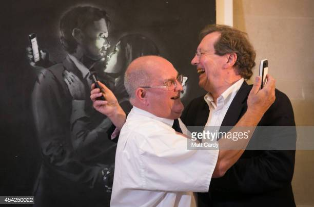 Denis Stinchcombe manager of Broad Plain Boys' Club and Bristol Mayor George Ferguson recreate the image on Banksy's mural 'Mobile Lovers' displayed...