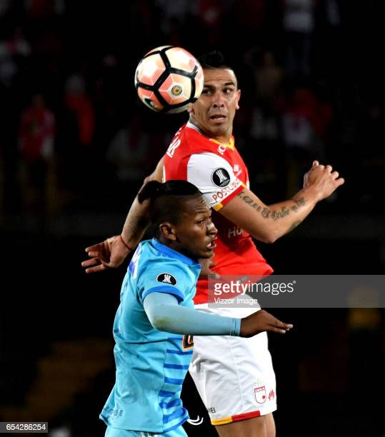 Denis Stracqualursi of Independiente Santa Fe goes for a header with Pedro Aquino of Sporting Cristal during a match between Independiente Santa Fe...