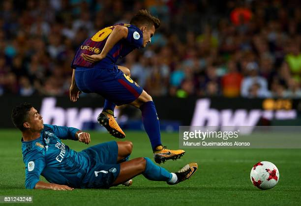 Denis Suarez of Barcelona is tackled by Cristiano Ronaldo of Real Madrid during the Supercopa de Espana Supercopa Final 1st Leg match between FC...